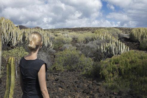 Spain, Tenerife, Malpais de Guimar, woman in volcanic landscape with cacti - PSTF00307
