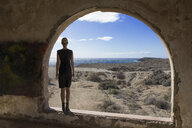 Spain, Tenerife, Abades, Sanatorio de Abona, woman standing at arched window in ghost town building - PSTF00313
