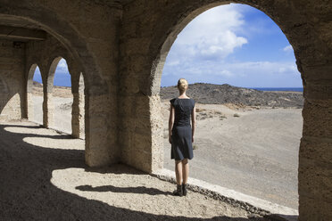 Spain, Tenerife, Abades, Sanatorio de Abona, woman standing at arched window in ghost town building - PSTF00319