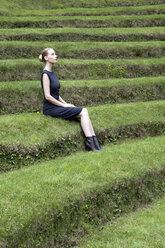 Italy, Alto Adige, Lana, woman sitting on grass-covered steps of natural open air theater - PSTF00325