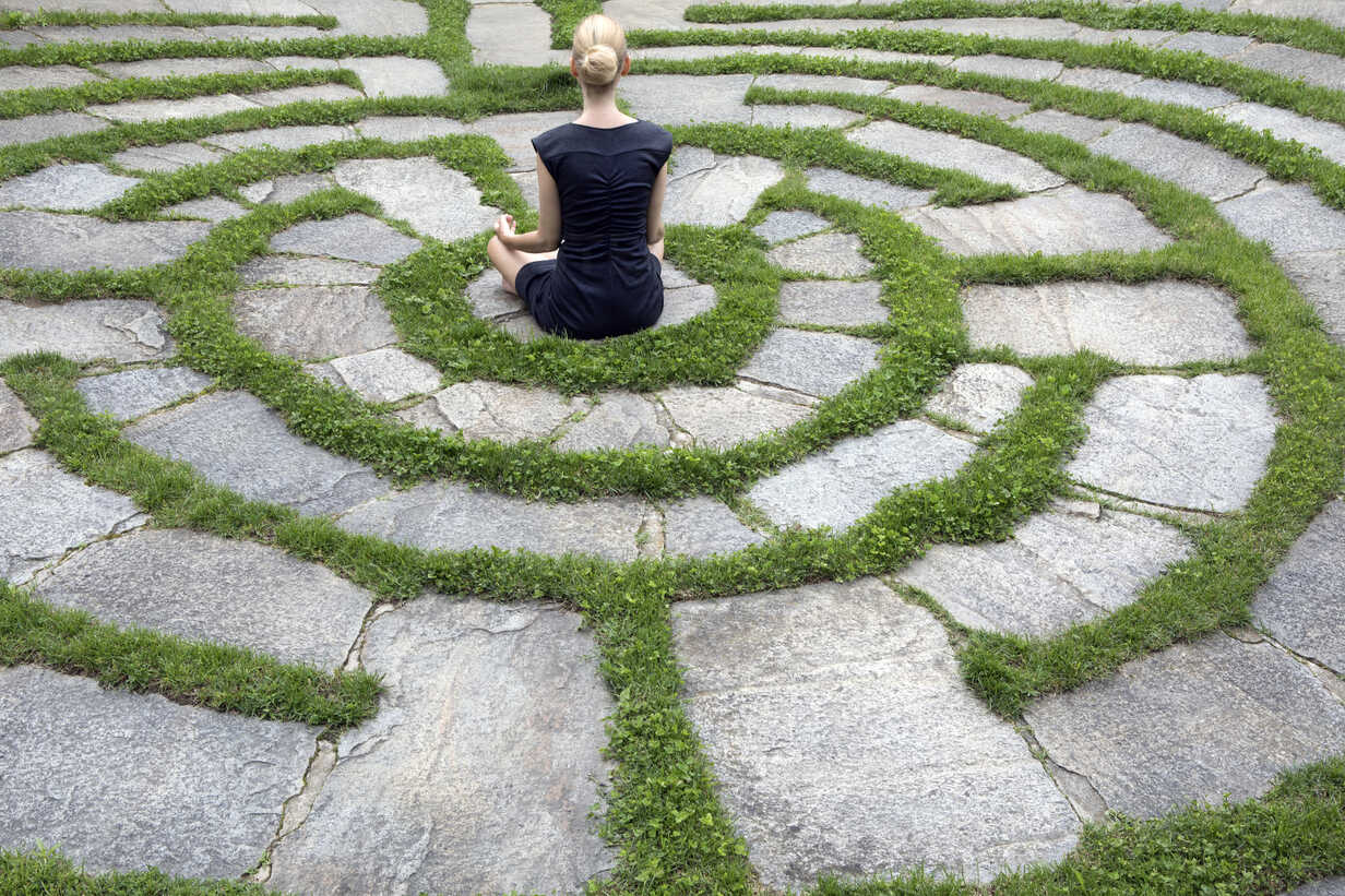 Italy, Alto Adige, Lana, woman sitting in natural open air maze meditating - PSTF00328 - Petra Stockhausen/Westend61