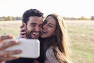 Happy couple taking a selfie in a park - IGGF00827