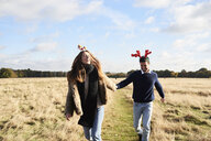 Happy carefree couple wearing Christmassy headdress in the countryside - IGGF00830