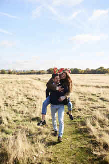 Happy carefree couple wearing Christmassy headdress in the countryside - IGGF00833