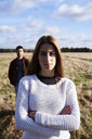 Young woman standing on a field with man behind her - IGGF00836