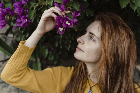 Spain, Canary Islands, Fuerteventura, profile of redheaded young woman with purple blossoms - AFVF02472