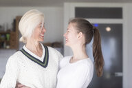 Laughing mother and adult daughter looking at each other - SGF02294
