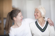 Smiling mother and adult daughter looking at each other - SGF02303