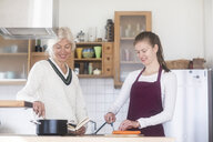 Mother and adult daughter cooking together at home - SGF02312