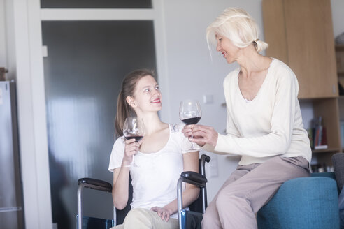 Mother and daughter in the wheelchair with a glass of red wine at home - SGF02339