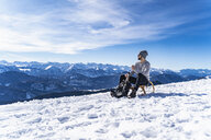 Germany, Bavaria, Brauneck, man in winter in the mountains having a break - DIGF05904