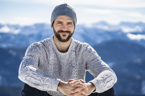 Germany, Bavaria, Brauneck, portrait of smiling man in winter in the mountains - DIGF05907