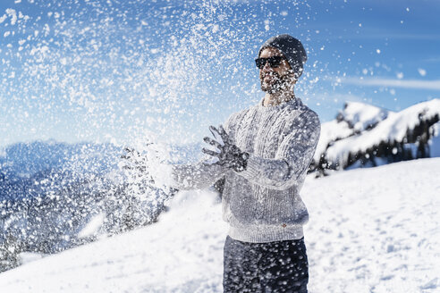 Germany, Bavaria, Brauneck, man in winter playing with snow in the mountains - DIGF05931