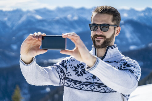 Germany, Bavaria, Brauneck, man in winter in the mountains taking a selfie - DIGF05937