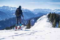 Germany, Bavaria, Brauneck, man on a ski tour in winter in the mountains - DIGF05940