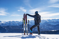 Germany, Bavaria, Brauneck, man on a ski tour in winter in the mountains having a break - DIGF05955