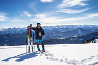 Germany, Bavaria, Brauneck, man on a ski tour in winter in the mountains having a break - DIGF05958