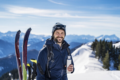 Germany, Bavaria, Brauneck, portrait of smiling man on a ski tour in winter in the mountains having a break - DIGF05961