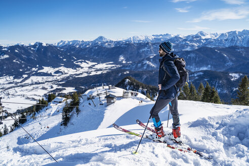 Germany, Bavaria, Brauneck, man on a ski tour in winter in the mountains enjoying the view - DIGF05964