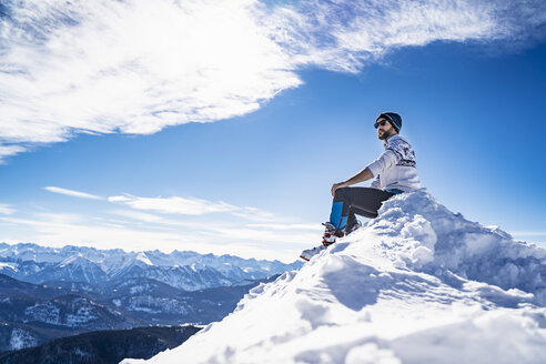 Germany, Bavaria, Brauneck, man in winter sitting on mountaintop - DIGF05967