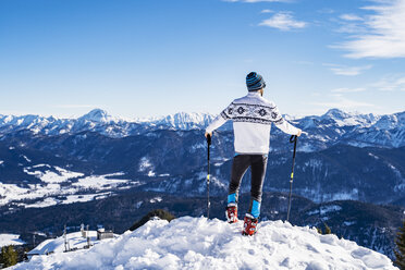 Germany, Bavaria, Brauneck, man in winter standing on mountaintop - DIGF05970