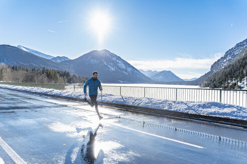 Germany, Bavaria, sportive man running on a road in winter - DIGF05973
