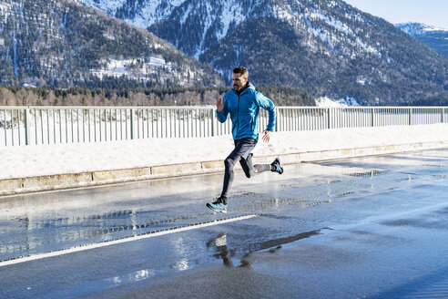 Germany, Bavaria, sportive man running on a road in winter - DIGF05976