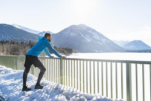 Germany, Bavaria, sportive man standing in winter on bridge - DIGF05979