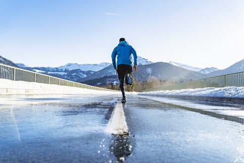 Germany, Bavaria, sportive man running on a road in winter - DIGF05982