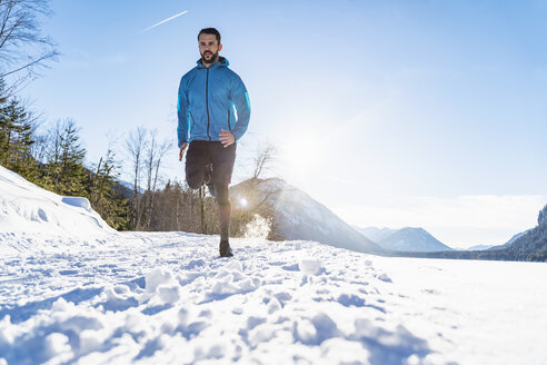 Germany, Bavaria, sportive man running through snow in winter - DIGF05985