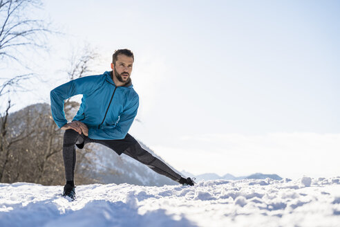 Germany, Bavaria, sportive man stretching in winter - DIGF05988
