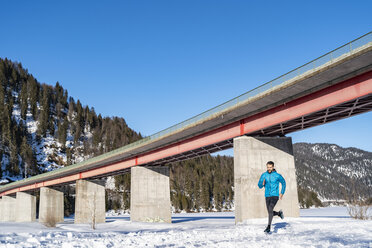 Germany, Bavaria, sportive man running at a bridge in winter - DIGF05991