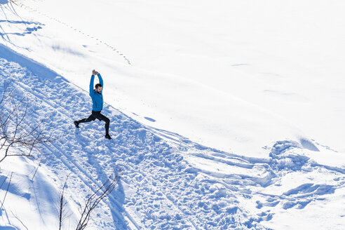 Germany, Bavaria, sportive man stretching in snow in winter - DIGF05997
