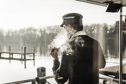 Man with a captain's hat standing on a housebpat, smoking pipe - MJRF00076
