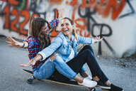 Two laughing friends sitting on longboard with arms outstretched - HMEF00251