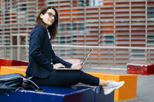 Businesswoman sitting outside office building in the city using laptop - JRFF02728
