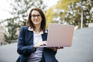 Portrait of smiling businesswoman in the city using laptop - JRFF02731