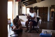 Father playing guitar and mother playing with little boy at home - IGGF00862
