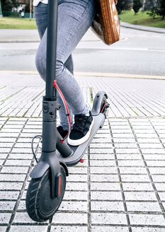 Close-up of young woman on electric scooter in the city - MGOF03953