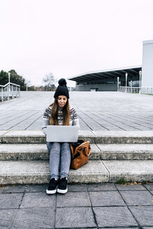 Young woman sitting outdoors on stairs using laptop - MGOF03956