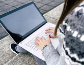 Close-up of woman sitting outdoors on stairs using laptop - MGOF03959