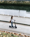 Young woman riding electric scooter on the street - MGOF03965