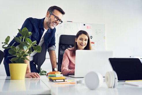 Two colleagues working together on laptop in office - BSZF00989