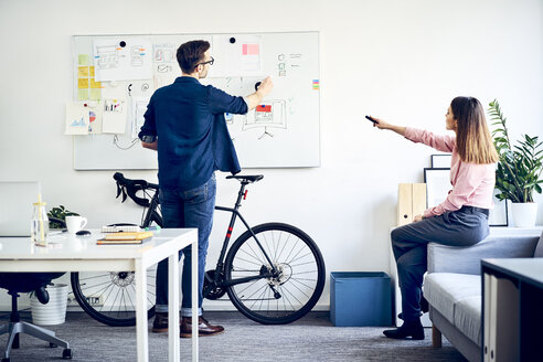 Two colleagues discussing at whiteboard in office - BSZF01004