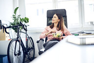 Businesswoman having lunch break in office sitting at desk - BSZF01010