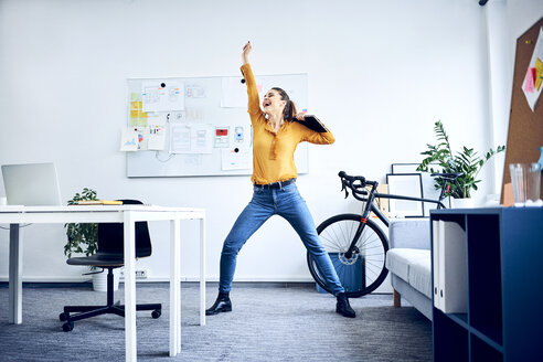 Happy young businesswoman cheering in office - BSZF01028
