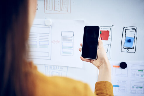 Close-up of businesswoman holding smartphone at whiteboard in office - BSZF01034