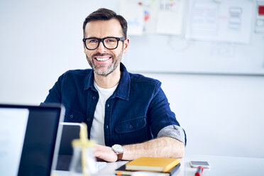 Portrait of casual businessman working at desk in office - BSZF01049