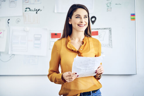 Smiling businesswoman with papers standing at whiteboard leading a presentation - BSZF01052