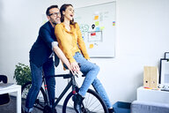Happy colleagues riding bicycle together in office - BSZF01058